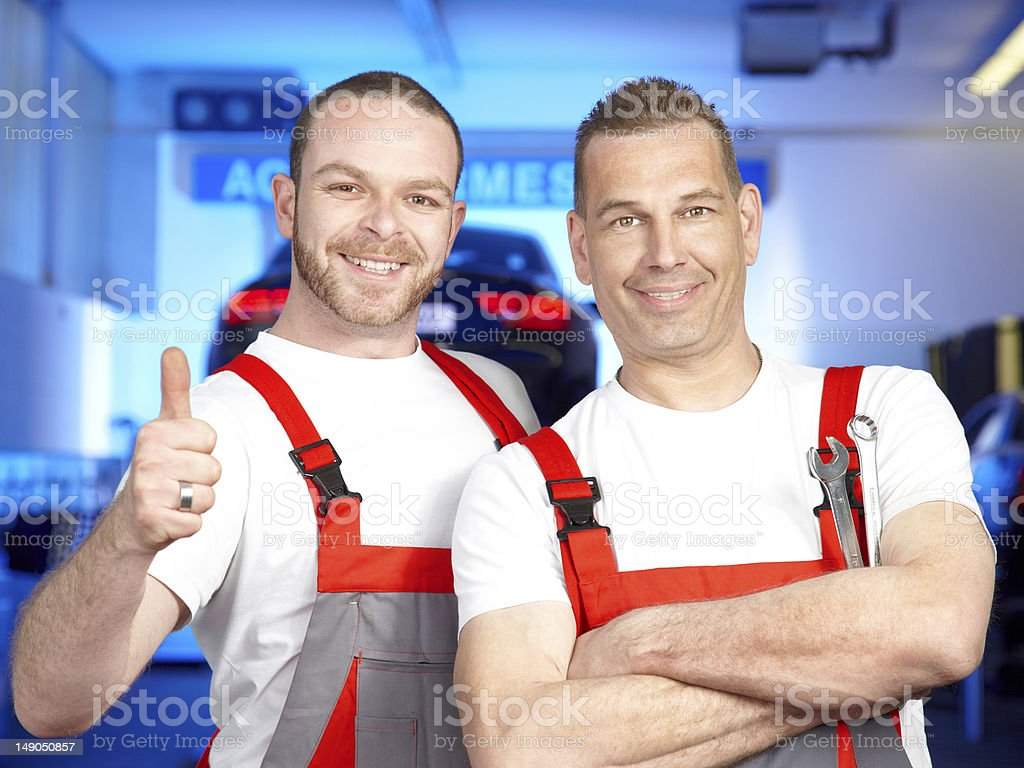 Two satisfied car mechanics at work in a garage royalty-free stock photo