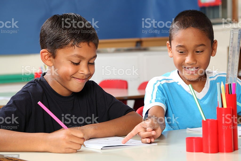 Two schoolboys helping each other learn in class during lessons royalty-free stock photo