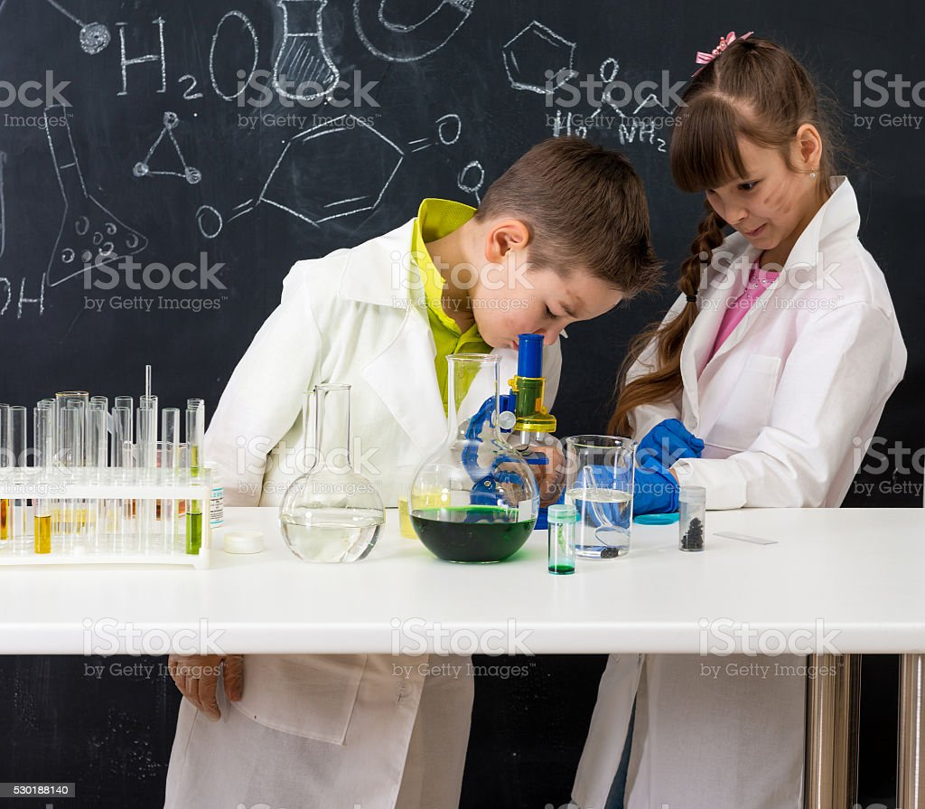 two schoolchildren watching chemical experiment stock photo