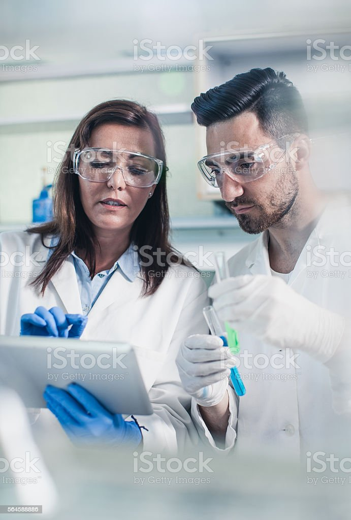 Two Scientist Discussing and Using a Digital Tablet stock photo