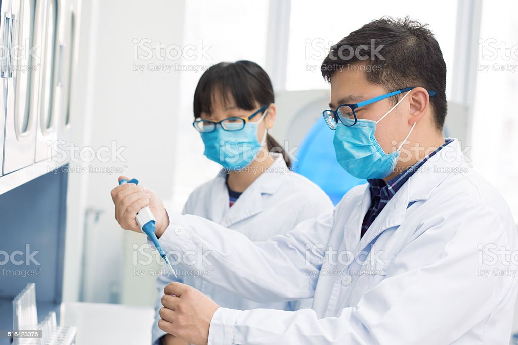Two scientists in a lab looking through microscope stock photo