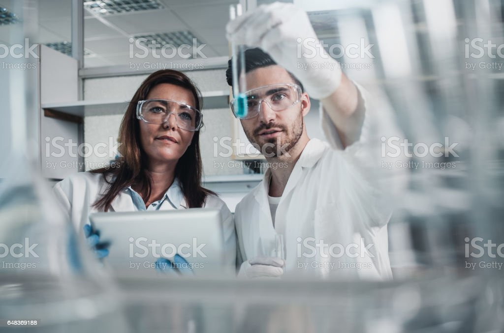 Two Scientists Looking at a Test Tube Filled With a Reagent stock photo
