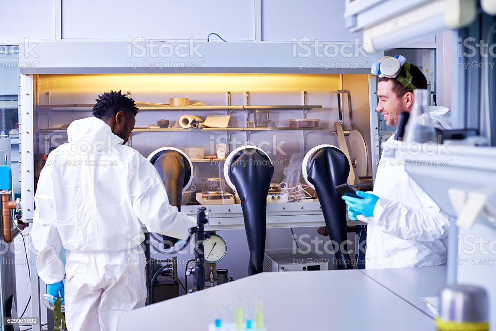 Two scientists working with glove box stock photo