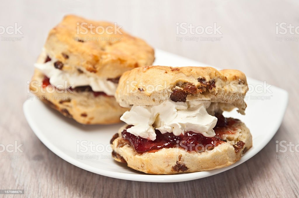 Two scones with jam on a white dish stock photo