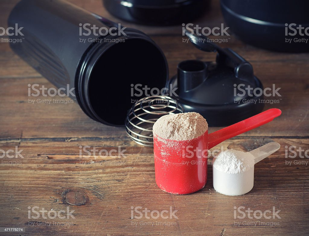 Two scoops of whey protein next to a black shaker cup stock photo