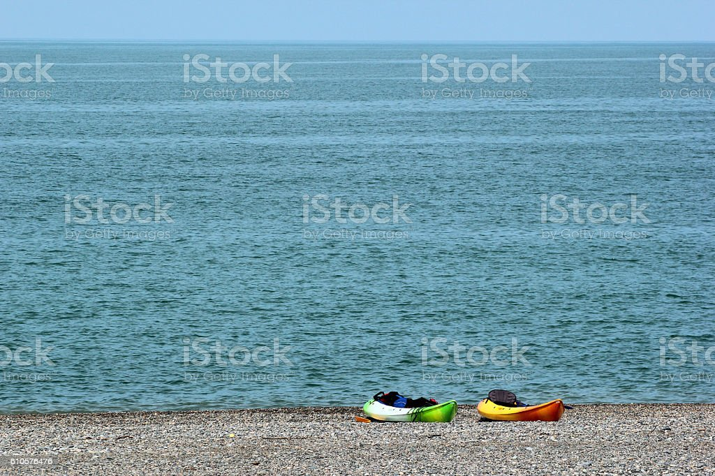 Two sea kayaks, paddles and life jackets on a beach stock photo