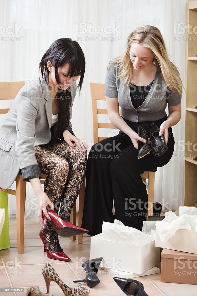 Two Seated Young Women Shopping in Retail Fashion Shoes Store royalty-free stock photo