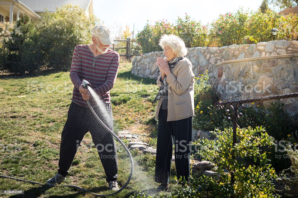 Two Senior Adults Watering with Garden Hose and Laughing stock photo