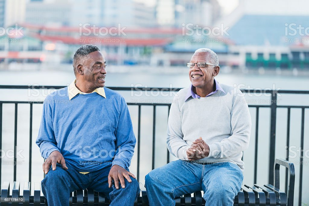 Two senior African American men on bench by waterfront stock photo