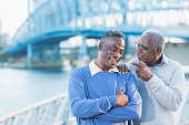 Two senior African American men on city waterfront