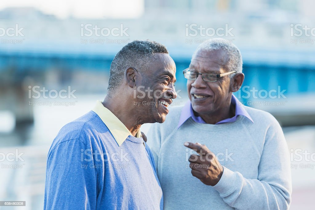Two senior African American men on city waterfront stock photo