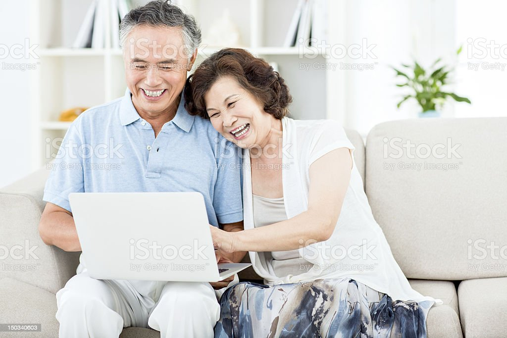 Two senior asian people using computer stock photo