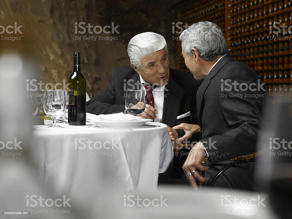 Two senior businessmen talking in restaurant, view across table royalty-free stock photo
