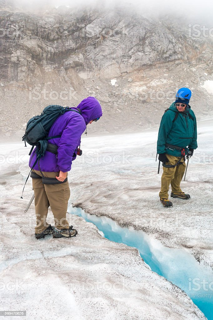 Two senior Caucasian adults stare into a crevasse stock photo