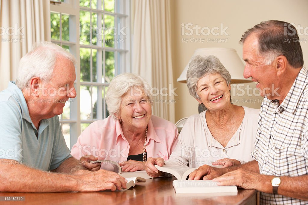 Two Senior Couples Attending Book Reading Group stock photo