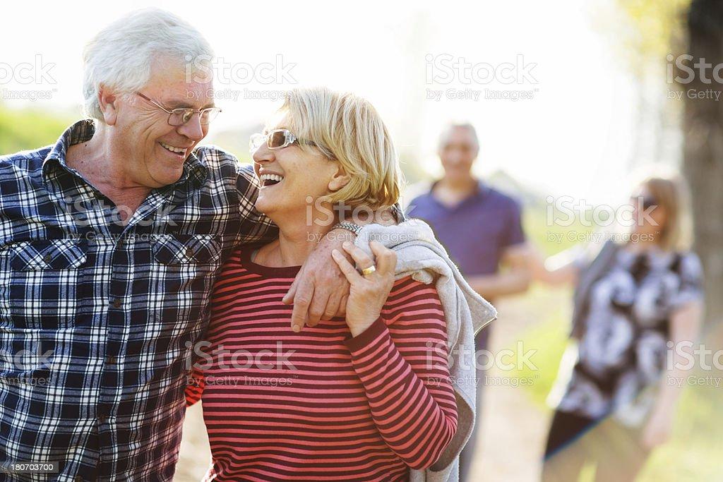 Two senior couples enjoy outdoor walk on sunny day royalty-free stock photo