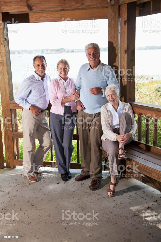 Two senior couples on deck overlooking water stock photo