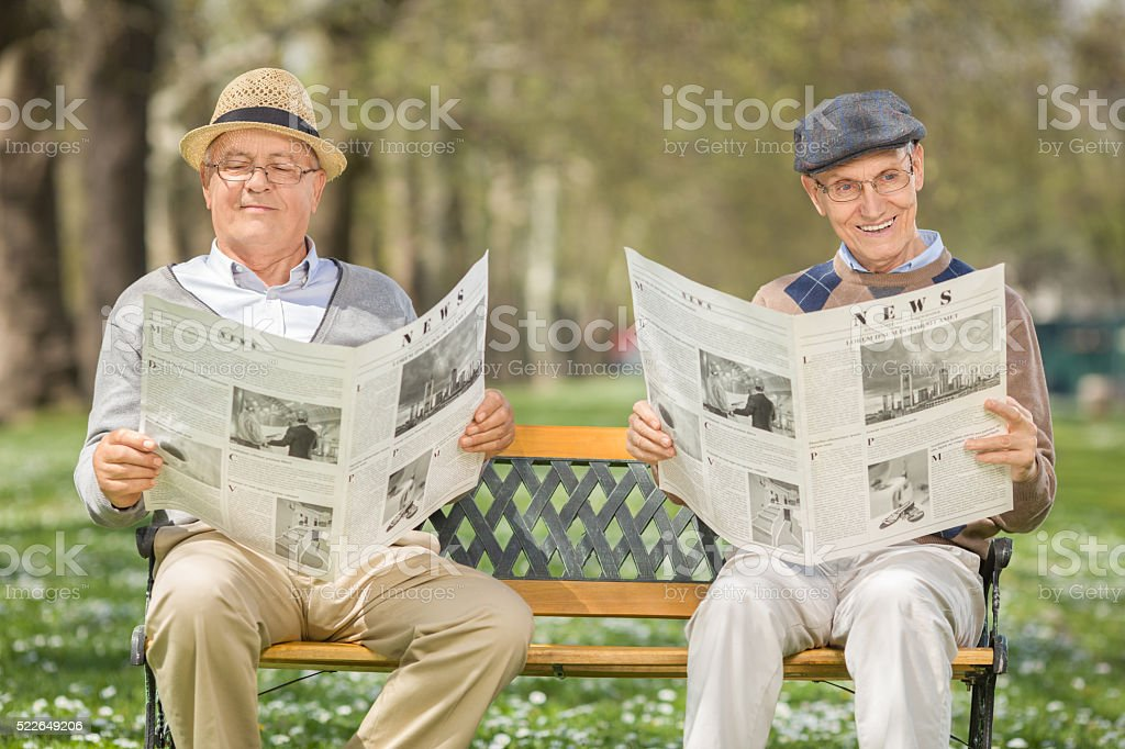 Two senior gentlemen reading the news stock photo