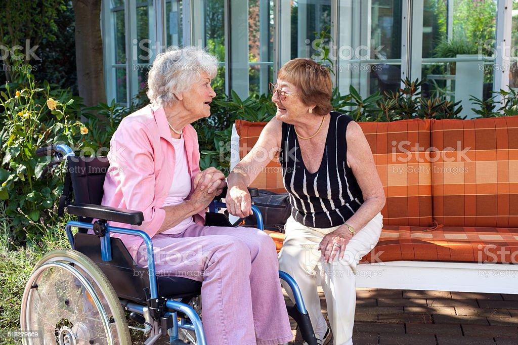 Two senior ladies chatting on a garden bench. stock photo