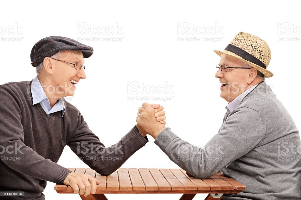 Two senior man having an arm wrestle competition stock photo