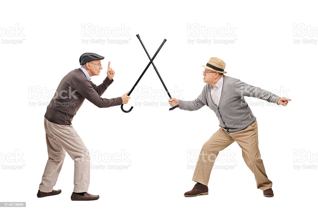 Two senior man in a sword fight with canes stock photo