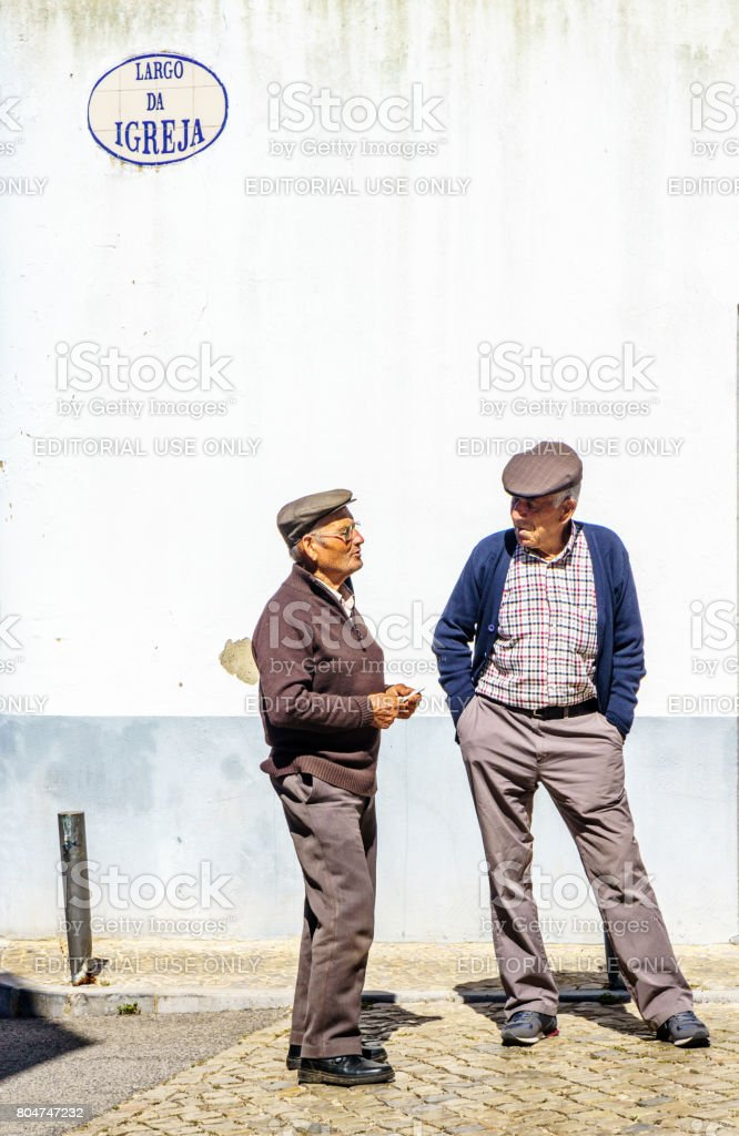 Two senior men chatting in Portuguese village of Alte stock photo