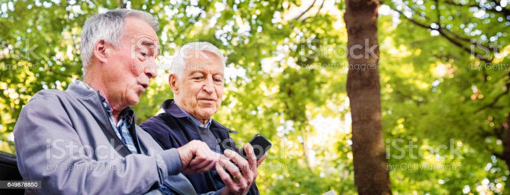 Two senior men enjoying time together in park stock photo