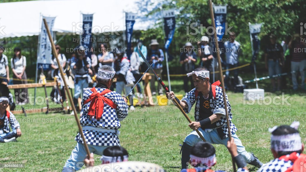 Two senior men fighting kendo in a field stock photo