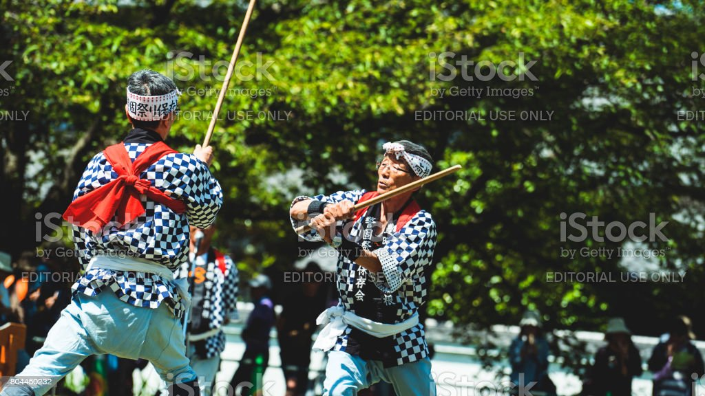 Two senior men fighting kendo style sports in a field stock photo