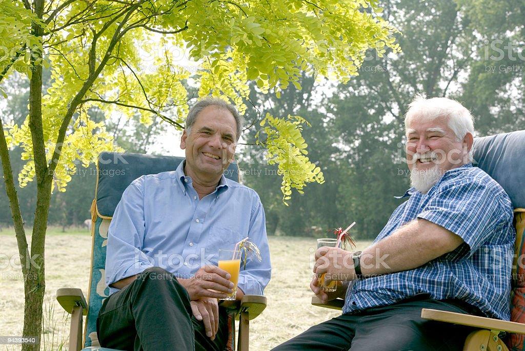 Two senior men with orange juice sitting under tree (XL) royalty-free stock photo