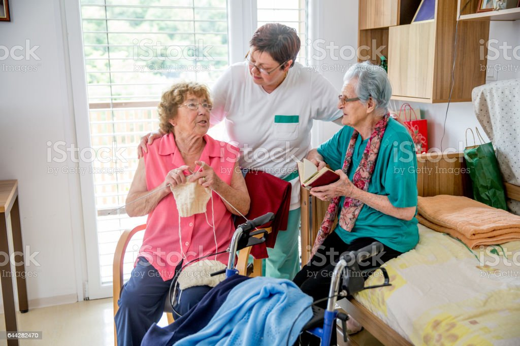 Two Senior Woman Socializing In Their Bedroom At The Elderly Center stock photo