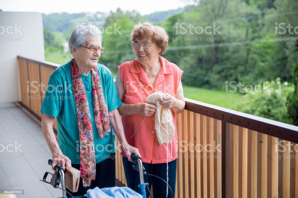 Two Senior Woman Socializing On The Balcony At The Elderly Center stock photo