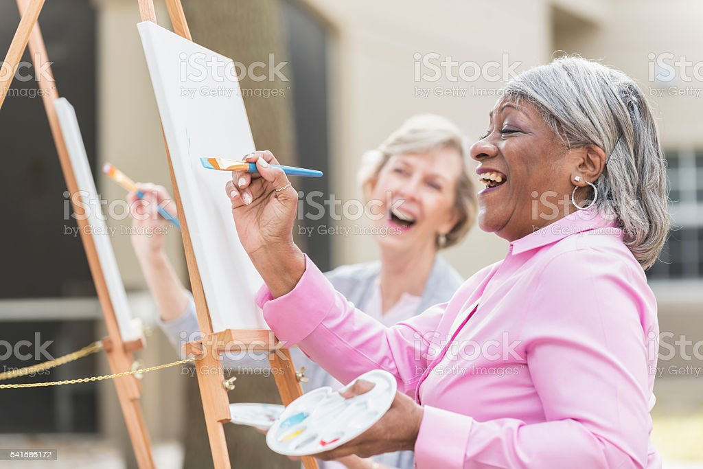 Two senior women having fun painting in art class stock photo