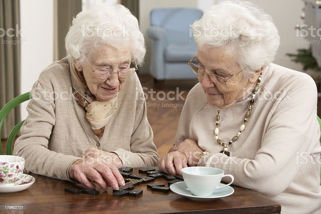 Two senior women playing dominoes at day care center stock photo