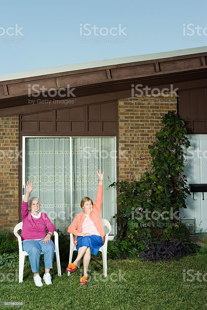 Two senior women sat in garden waving stock photo