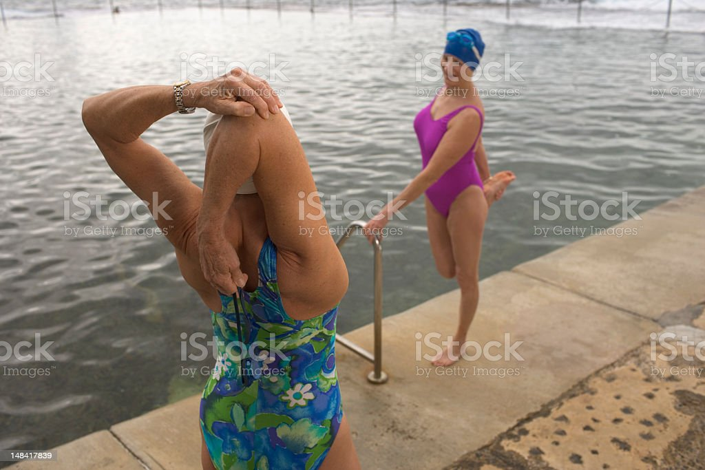 Two senior women stretching at side of infinity pool royalty-free stock photo