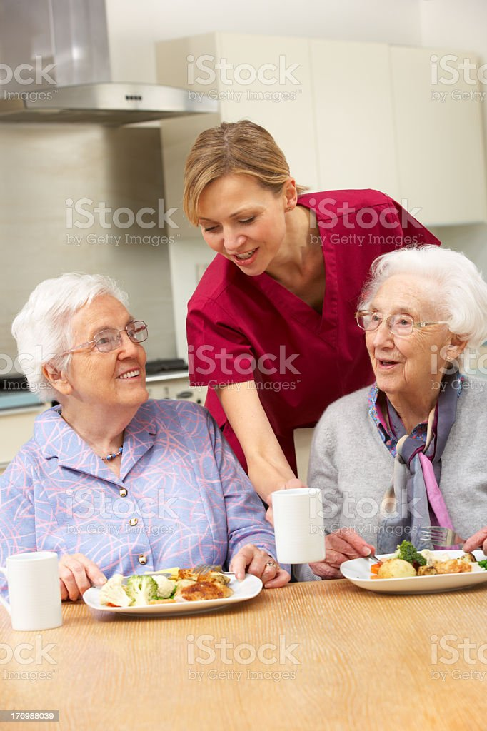 Two senior women with a caregiver enjoy a meal at home royalty-free stock photo