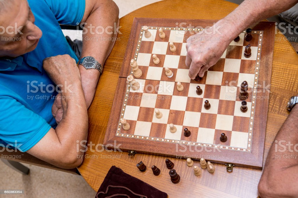 Two Seniors Playing Chess In The Elderly Day Care Center stock photo
