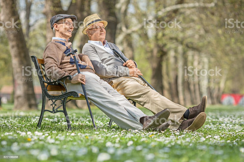 Two seniors sitting and relaxing in a park stock photo