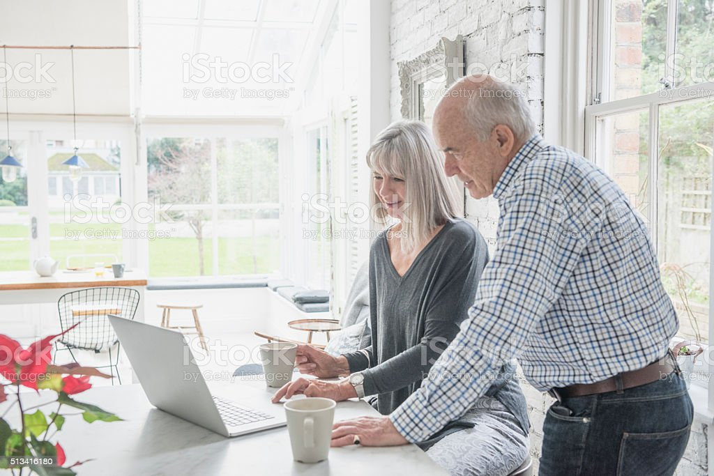 Two seniors using a laptop at home in modern conservatory stock photo