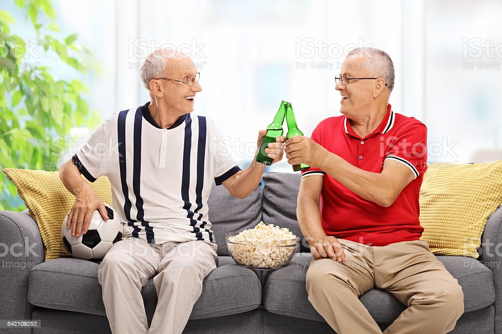 Two seniors watching soccer and drinking beer stock photo