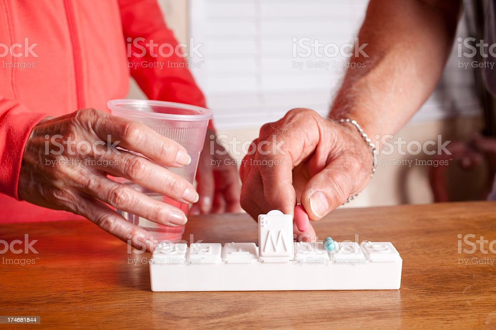 Two seniors with pill organizer and medications royalty-free stock photo
