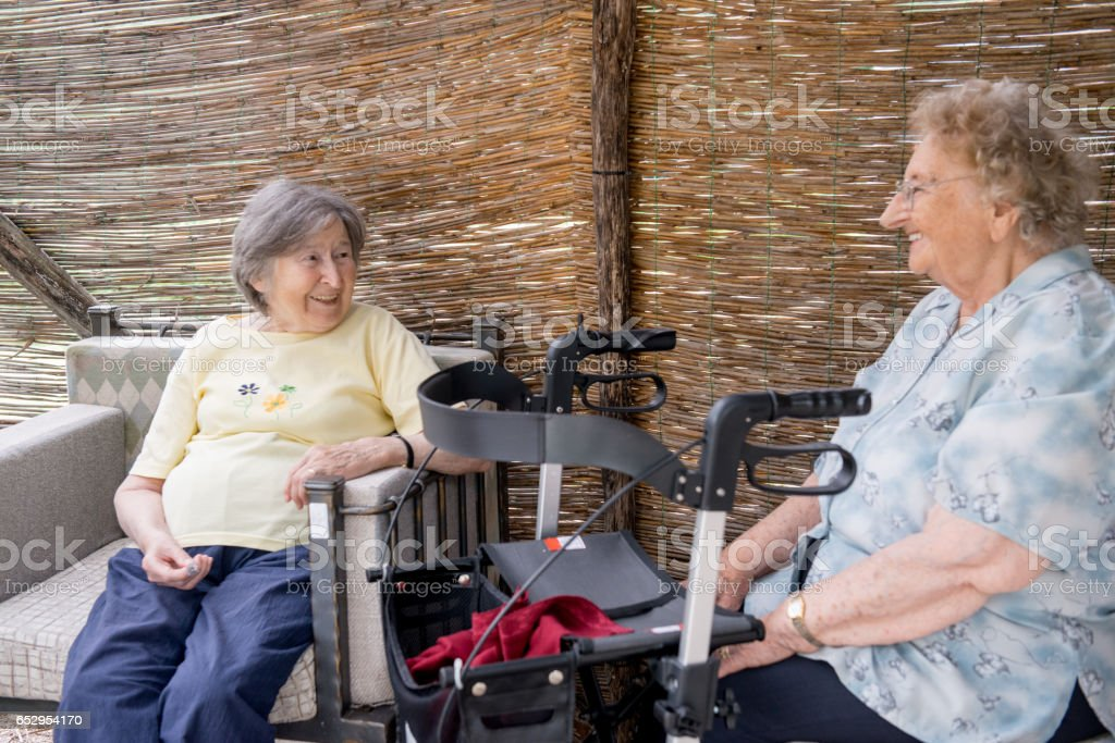 Two Seniors Women Relaxing In The Shade At The Nursery Home stock photo