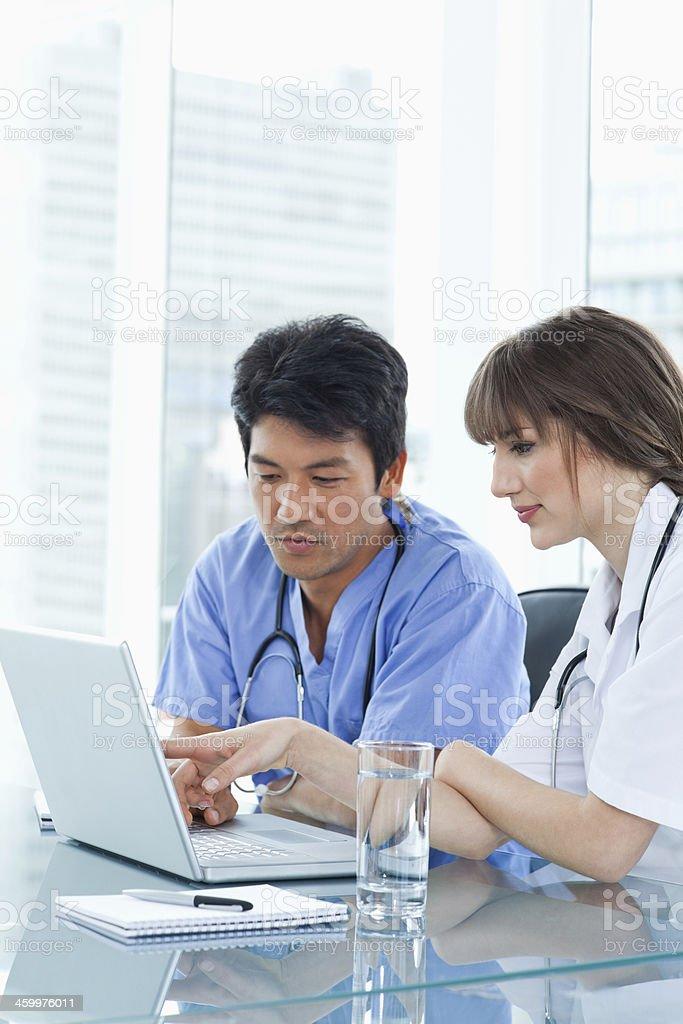 Two serious nurses communicating around the laptop stock photo