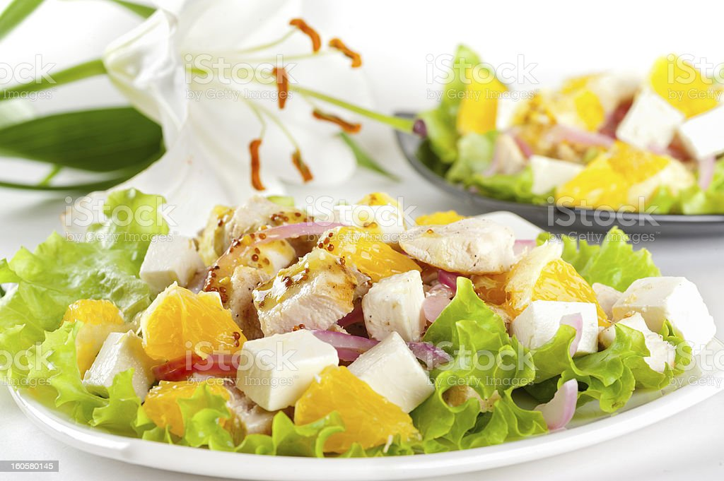 Two servings of salad with chicken, feta cheese, orange royalty-free stock photo