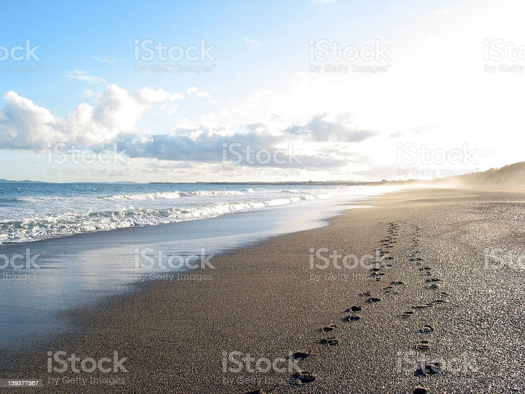 Two sets of beach footprints walking towards the sun stock photo