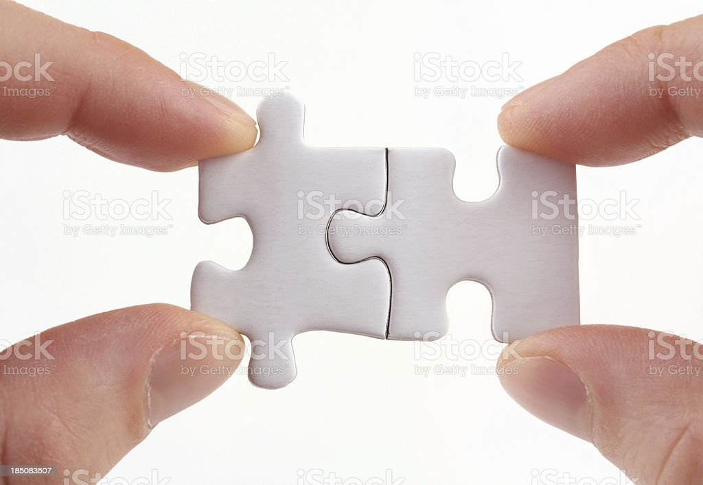 Two sets of fingers holding two puzzle pieces together royalty-free stock photo
