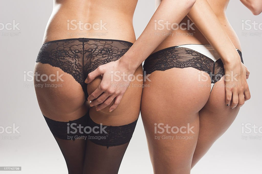 Two sexy women touching each others bottoms royalty-free stock photo