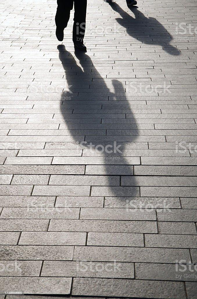 Two Shadow Figures Walking on Brick Road Walkway stock photo