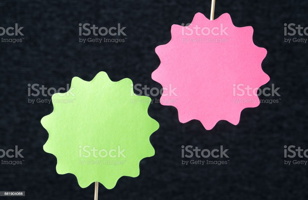Two shaped circles cut from cardboard on a wooden stick. Price, promotion or special offer signs. Template for round paper badge, label, plague or design elements on dark background and copy space. stock photo
